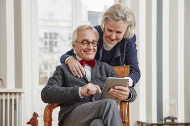 Smiling senior couple using tablet - RHF01735