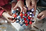 Hands of grandfather and grandchildren assembling molecular model - RHF01738