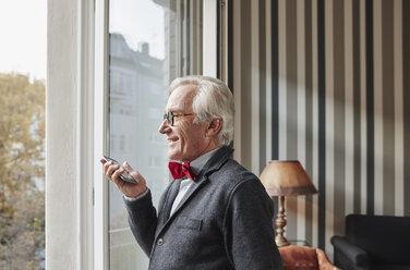 Senior man using cell phone at the window - RHF01747