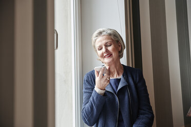 Senior woman using cell phone at the window - RHF01762