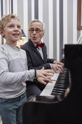 Grandfather and grandson playing piano and singing - RHF01765