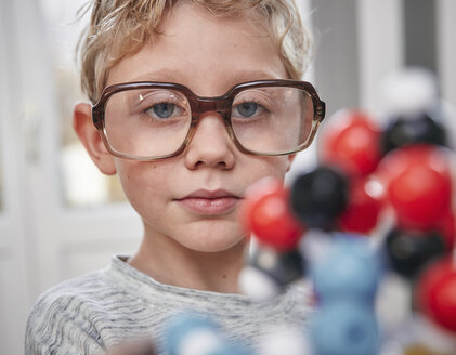 Boy wearing oversized glasses looking at molecular model - RHF01774