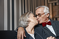 Senior couple kissing on couch - RHF01777