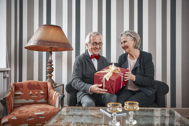 Happy senior couple sitting on couch with gift - RHF01780