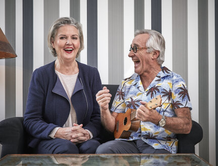 Happy senior couple with man in Hawaiian shirt playing ukulele - RHF01786