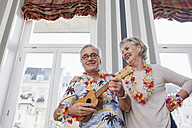 Happy senior couple with man in Hawaiian shirt playing ukulele - RHF01789