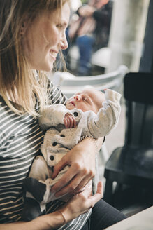 Smiling mother holding her sleeping baby in cafe - MFF03411