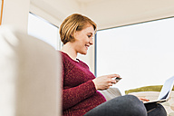 Smiling pregnant woman on couch shopping online - UUF09588