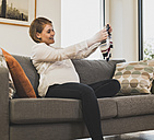 Pregnant woman on couch holding baby clothes - UUF09594