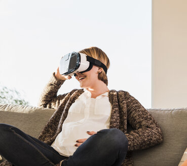 Pregnant woman on couch wearing VR glasses - UUF09603