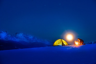 Senior man camping in snow-covered landscape at full moon - HHF05487