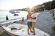Senior couple dancing together on a boat lying on the beach at evening twilight - HAPF01261