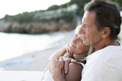 Senior couple relaxing together on the beach at evening twilight - HAPF01264