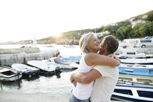 Happy senior couple on quai hugging at evening twilight - HAPF01267