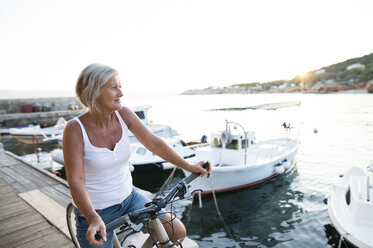 Senior woman with bicycle on a jetty - HAPF01270