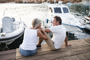 Senior couple sitting on jetty - HAPF01273
