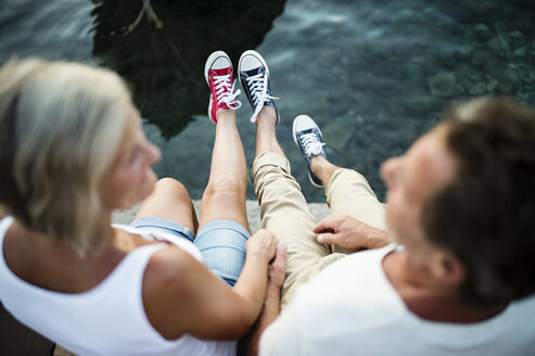 Senior couple sitting on jetty wearing sneakers - HAPF01276
