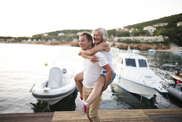 Senior man giving his wife a piggyback ride on a jetty - HAPF01279