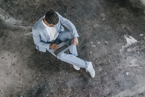 Businessman sitting on concrete floor using laptop - KNSF00829