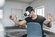 Man sitting on chair in empty loft wearing VR glasses - KNSF00841