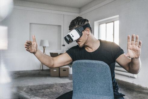 Man sitting on chair in empty loft wearing VR glasses - KNSF00841