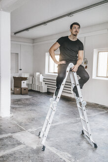 Man sitting on ladder in empty loft - KNSF00844