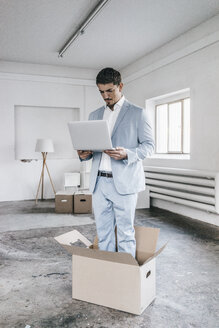Businessman using laptop inside cardboard box in empty loft - KNSF00850
