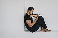Man sitting in niche using tablet - KNSF00865
