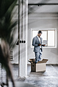 Businessman using laptop inside cardboard box in empty loft - KNSF00871