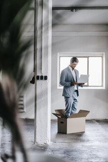 Businessman using laptop inside cardboard box in empty loft - KNSF00871