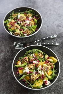 Two bowls of avocado salad with rocket, pomegranate seed, kaki, feta and walnuts - SARF03101