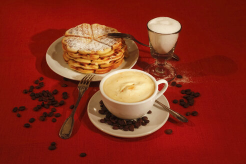 Cup of coffee, stack of waffles and glass of sugar on red ground - JTF00796