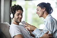 Young couple at home with smartphone and headphones - ZEF12025