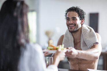 Smiling young couple at home eating sandwiches - ZEF12028
