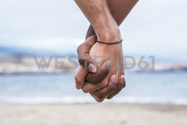 Close-up of two hands connected on the beach - SIPF01207