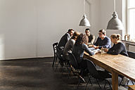 Coworkers having a meeting in modern office - TCF05286