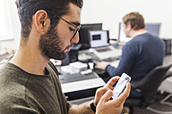 Young man using smartphone in modern office with coworker in background - TCF05295