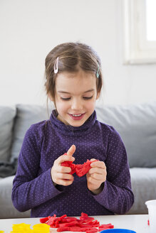Little girl kneading red modeling clay - LVF05771