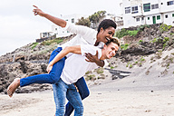 Young couple pretending to fly on a beach - SIPF01216