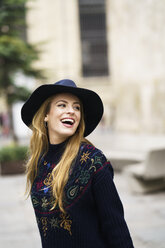 Portrait of laughing young woman wearing blue hat - KKAF00226