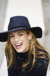 Portrait of laughing young woman wearing blue hat - KKAF00229