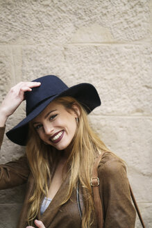 Portrait of smiling woman wearing leather jacket and blue hat - KKAF00241