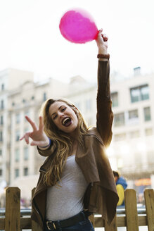 Portrait of happy young woman with balloon showing victory sign - KKAF00247