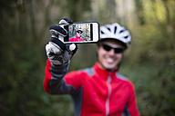 Mountain biker taking selfie with his smart phone - RAEF01617