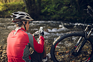 Mountain biker sitting at river, using smart phone - RAEF01623