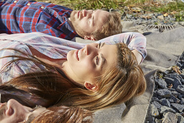 Young couple lying on a blanket outdoors - FMKF03361