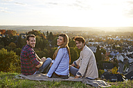 Happy friends sitting on a hill above a town - FMKF03379