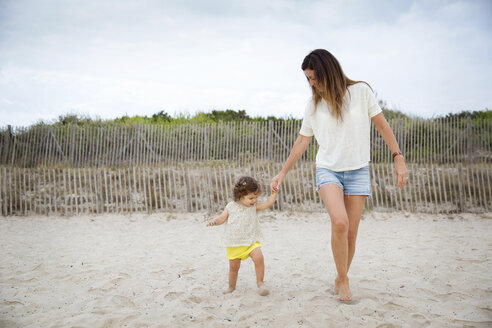 Mother with little daughter walking on the beach - LITF00444