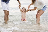 Parents playing in the sea with their little girl - LITF00459