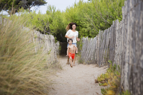 Happy mother and son running on beach path - LITF00462